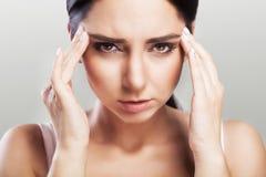 Hoofdpijn en strenge spanning ervaring Pijnlijk gevoel in het hoofd moeheid Het concept gezondheid op een grijze achtergrond Royalty-vrije Stock Afbeeldingen