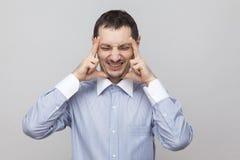 Hoofdpijnpijn Portret van boze varkenshaarzakenman in klassiek blauw overhemd die houdend zijn pijnlijke hoofd, gesloten ogen bev royalty-vrije stock fotografie