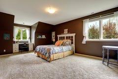 Hoofdslaapkamer in donkere bruine kleur met bureaugebied Royalty-vrije Stock Fotografie