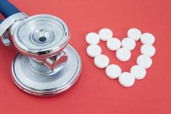 Hoofdstethoscoop en vorm van het menselijke die hart, met witte pillen op rode achtergrond wordt gevoerd Stethoscoop en hart van  Stock Fotografie