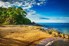 Hoofdstrand in Palminham met rotsen en bomen tijdens zonsondergang Royalty-vrije Stock Foto