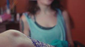 Hoofdtatoegering in medische steriele handschoenen die een tatoegering vormen stock videobeelden