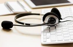 Hoofdtelefoon en toetsenbord op workdesk voor call centreconcept Stock Afbeelding