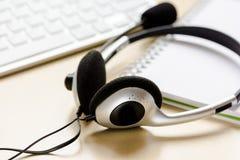 Hoofdtelefoon en toetsenbord op workdesk voor call centreconcept Royalty-vrije Stock Afbeeldingen