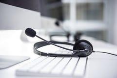 Hoofdtelefoon met microfoon op computertoetsenbord Royalty-vrije Stock Afbeelding