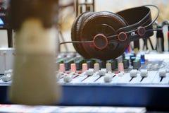 Hoofdtelefoon op analoge mixer in uitzendingsruimte stock afbeeldingen