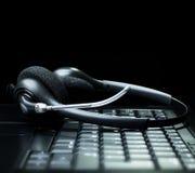 Hoofdtelefoon op een laptop computertoetsenbord stock afbeeldingen