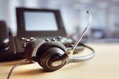 Hoofdtelefoonhoofdtelefoons en telefoon in call centre stock foto