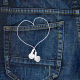 Hoofdtelefoons in een achterzak van jeans Stock Foto