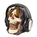 Hoofdtelefoons gezet op een ceramisch schedelhoofd Stock Foto
