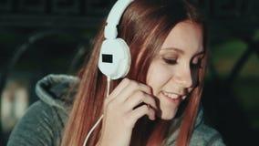hoofdtelefoons Het mooie meisje ontspannen en luistert muziek in de hoofdtelefoons in het stadspark Vrouw in de hoofdtelefoons stock videobeelden
