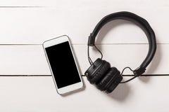 Hoofdtelefoons met smartphone op houten achtergrond royalty-vrije stock afbeelding