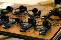 Hoofdtelefoons voor gelijktijdig vertaalmateriaal worden gebruikt dat stock foto