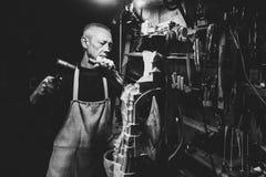 Hoofdtimmermans 50 - 55 jaar oud creeert houten beeldhouwwerk in de workshop stock afbeelding