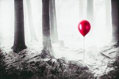 Hoog contrastbeeld van een rode ballon in het hout stock fotografie