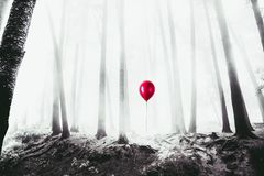 Hoog contrastbeeld van een rode ballon in het hout stock foto