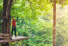 Hoog de draadpark van avonturenzipline - mensen op cursus in berghelm en veiligheidsmateriaal Stock Foto