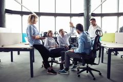 Hoog-vijf! vrolijke jonge bedrijfsmensen die hoog-vijf geven terwijl hun hen bekijken en collega's die glimlachen stock foto