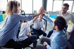 Hoog-vijf! vrolijke jonge bedrijfsmensen die hoog-vijf geven terwijl hun hen bekijken en collega's die glimlachen stock foto's