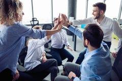 Hoog-vijf! vrolijke jonge bedrijfsmensen die hoog-vijf geven terwijl hun hen bekijken en collega's die glimlachen stock afbeeldingen