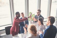 Hoog-vijf vrolijke jonge bedrijfsmensen die hoog-vijf geven terwijl hun hen bekijken en collega's die glimlachen Stock Foto