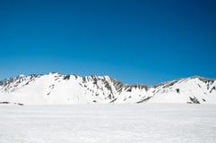 Hooggebergte onder sneeuw met duidelijke blauwe hemel stock foto