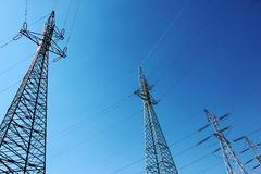 Hoogspannings elektrische torens onder blauwe hemel Royalty-vrije Stock Afbeelding