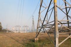 Hoogspanningspost en elektrische centraleachtergrond Royalty-vrije Stock Afbeeldingen