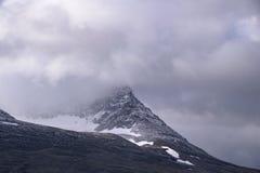Hoogste berg behandeld in regenwolken met gletsjer onder de erwt stock afbeeldingen