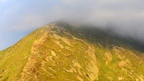 Hoogste bergpiek behandelde wolken stock footage