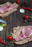 Hoogste de halslapje vlees van het menings Vers ruw varkensvlees met kruiden op het kraftpapier-document de donkere houten achter Stock Foto's