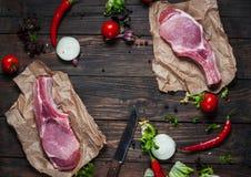 Hoogste de halslapje vlees van het menings Vers ruw varkensvlees met kruiden op het kraftpapier-document de donkere houten achter Stock Afbeeldingen