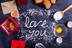 Hoogste de room van het meningsschuimgebakje het van letters voorzien Liefde u op de zwarte steenachtergrond met ingrediënten, bl Royalty-vrije Stock Fotografie