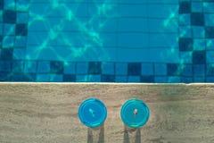Hoogste de vakantieachtergrond van het meningsstrand met twee cocktails in het glas dichtbij zwembad van de meerminstaart in luxu stock afbeeldingen