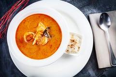Hoogste die mening over tom yum soep in witte plaat met rijst wordt gediend soep met garnalen, zeevruchten, kokosmelk en Spaanse  royalty-vrije stock fotografie