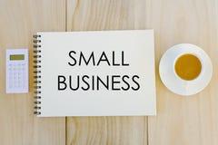 Hoogste die mening van calculator, een kop van koffie en notitieboekje met Small Business op houten achtergrond wordt geschreven  stock fotografie