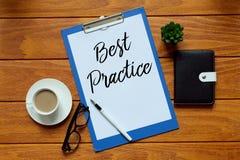 Hoogste die mening van een kop van koffie, pen, zonnebril, notitieboekje, installatie en document met Best practice op houten ach royalty-vrije stock foto