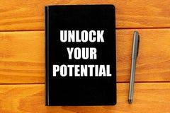 Hoogste die mening van pen en notitieboekje met Unlock uw potentieel op houten achtergrond wordt geschreven Bedrijfs concept stock fotografie