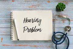 Hoogste die mening van stethoscoop, installatie, pen en notitieboekje met Hoorzittingsprobleem wordt geschreven aangaande houten  stock afbeeldingen
