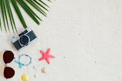 Hoogste die mening van strandzand met kokosnotenbladeren, camera, armband van zeeschelpen, zonnebril, shells en zeester wordt gem stock foto's