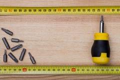 Hoogste die meningsschroevedraaier met metingsband wordt geplaatst op houten lijst Royalty-vrije Stock Afbeelding