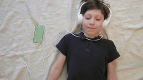 Hoogste leuke mening van weinig jongen die aan muziek luisteren die hoofdtelefoons van zijn smartphone dragen stock footage