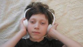 Hoogste leuke mening van weinig jongen die aan muziek luisteren die zijn hoofdtelefoons houden bekijkend de camera stock videobeelden