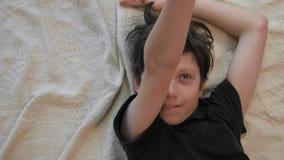 Hoogste leuke mening van weinig jongen die op het tapijt leggen en met zijn stuk speelgoed vliegtuig spelen stock videobeelden
