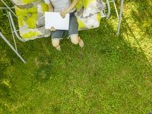 Hoogste luchtmening van freelancer met een laptop zitting op schommeling op grasgebied stock fotografie