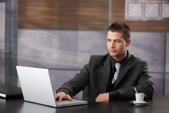 Hoogste manager die in buitensporig bureau werkt stock afbeelding