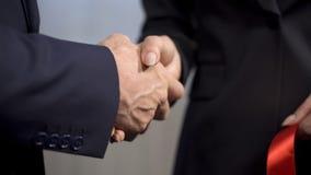 Hoogste manager het schudden handen met vrouwelijke partner na lintknipsel royalty-vrije stock afbeelding