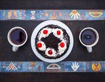 Hoogste mening Cake met kersen, chocoladeschilfers en twee kop theeën op houten lijst met Egyptisch patroon Vlak leg royalty-vrije stock afbeeldingen