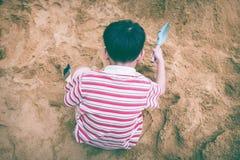 Hoogste mening De aanbiddelijke Aziatische jongen heeft pret het graven in het zand op su Royalty-vrije Stock Fotografie