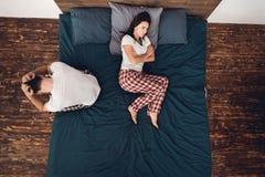 Hoogste mening De beledigde vrouw in pyjama ligt op bed, draaiend haar terug naar de zittings volwassen mens stock foto's